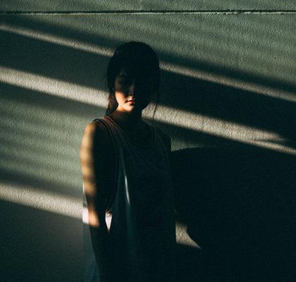 Frau steht im Schatten an Wand