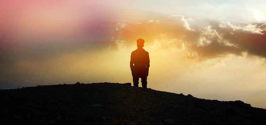 Mann steht bei Sonnenuntergang an Klippe