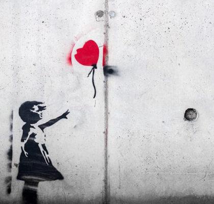 Mädchen greift nach Luftballon