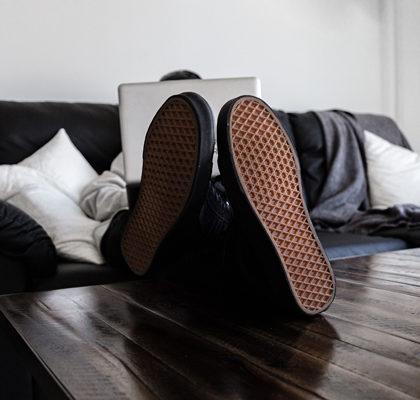 Mann sitzt mit Laptop auf dem Schoß auf Sofa