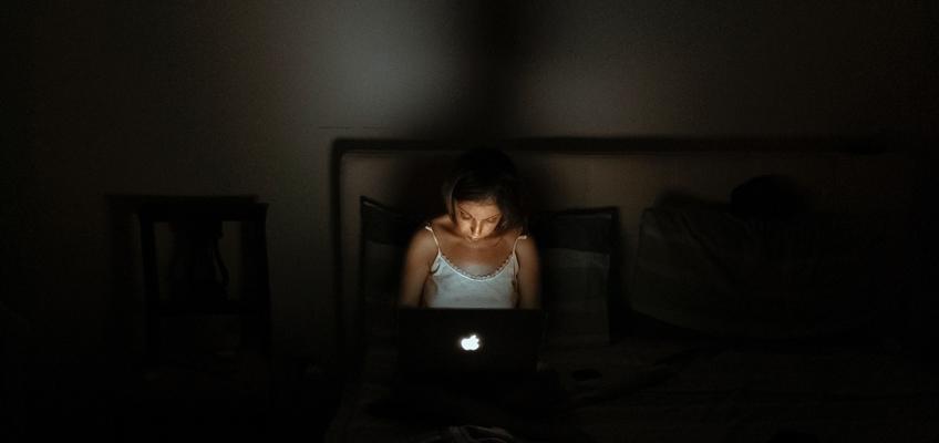 Frau sitzt auf Bett mit Laptop auf den Beinen