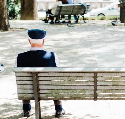 Rentner sitzt auf Parkbank