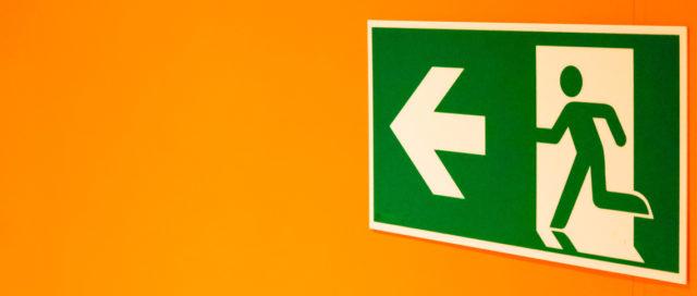 Fluchtweg-Schild auf oranger Wand