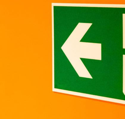 Schild Fluchtweg auf oranger Wand
